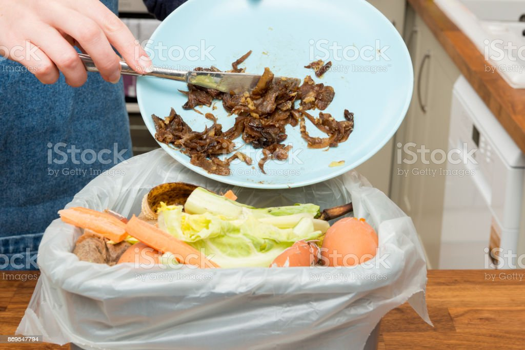 Leftovers from Plate Thrown into Bin Filled with Food Scraps stock photo