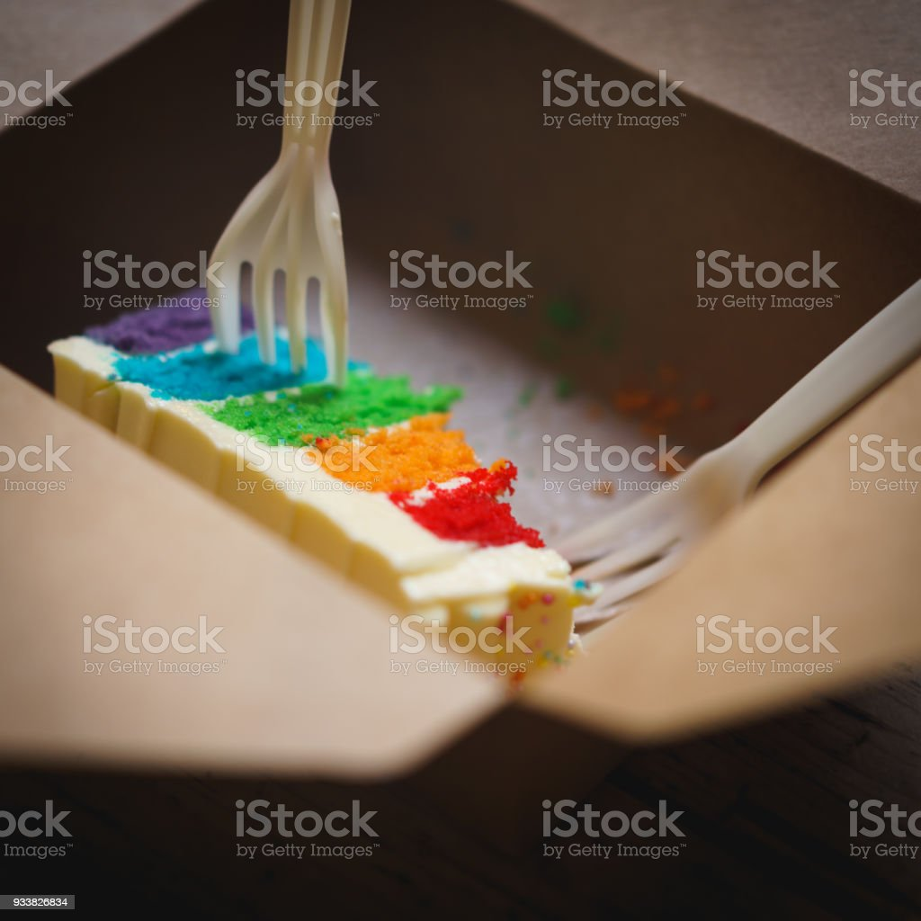 Leftovers Of A Rainbow Cake With White Butter Frosting In A Brown