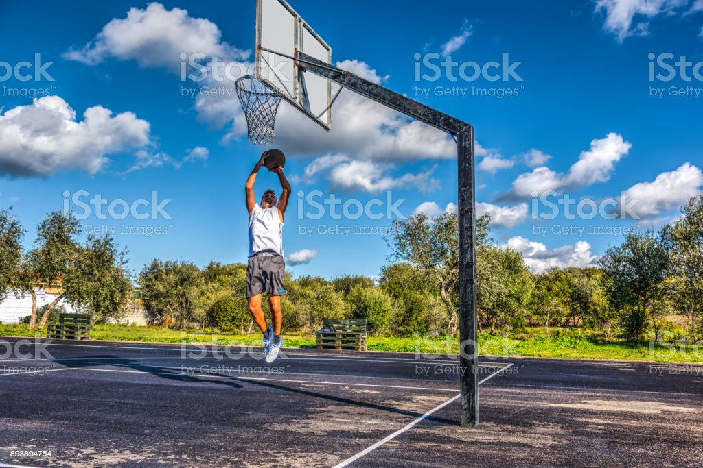 Lefty basketball player jumping to the basket stock photo