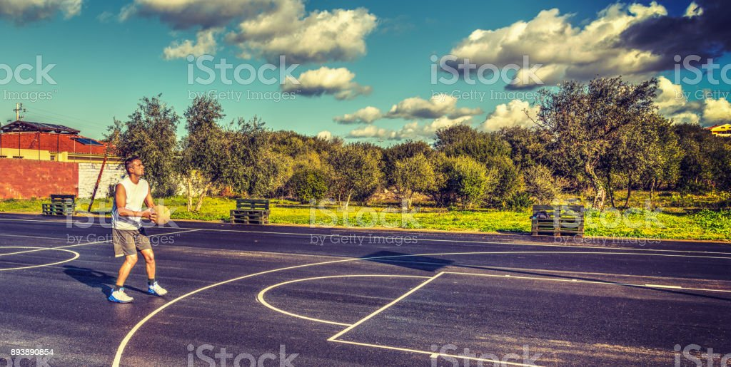Lefty basketball player loading a three point shot stock photo