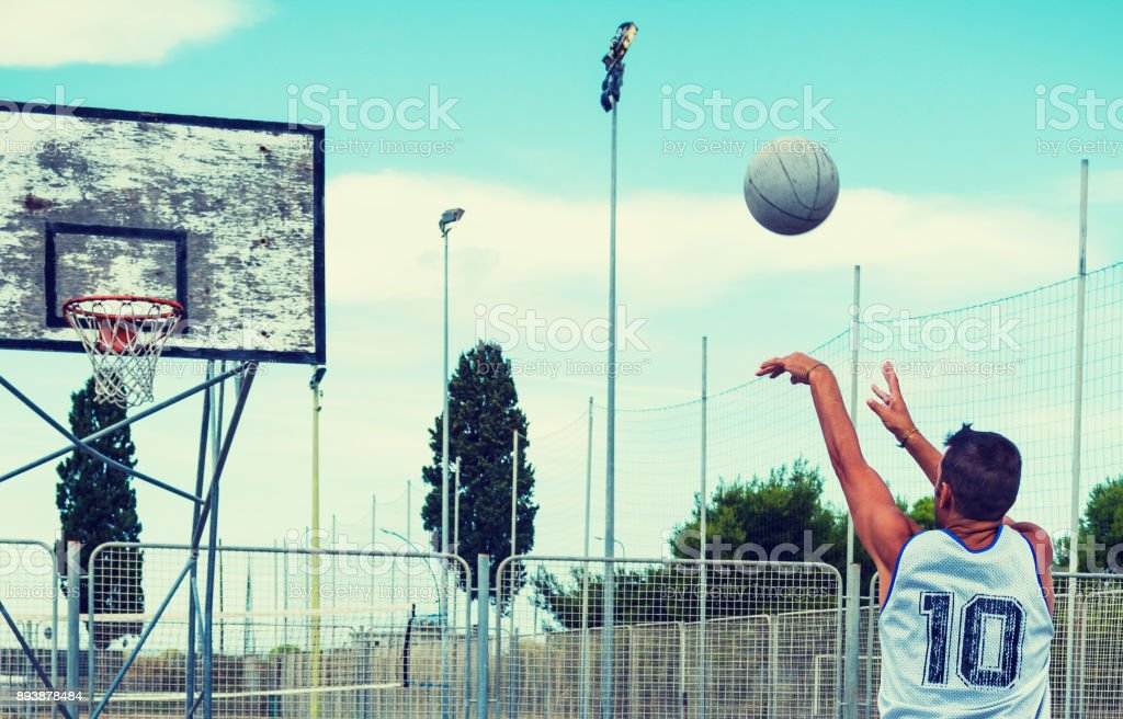 Lefty basketball player shooting in a playground stock photo
