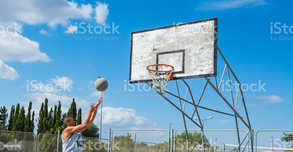 Lefty basketball players shooting in a playground stock photo