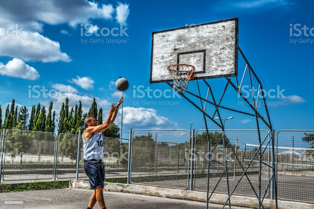 Lefty jump shot in a playground on a cloudy day stock photo