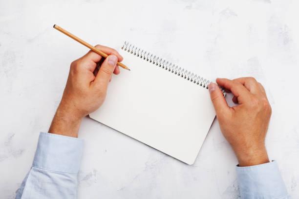 lefty écrit dans propre cahier sur la vue de dessus de table blanche. journée internationale de gauchers. - gaucher photos et images de collection