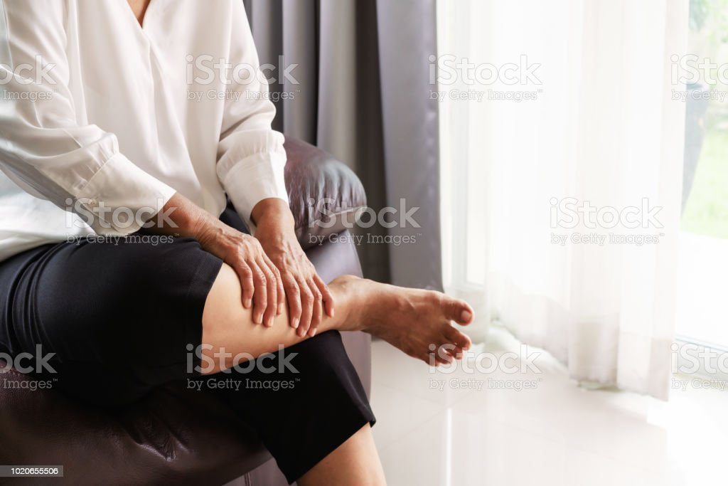 leg cramp, senior woman suffering from leg cramp pain at home, health problem concept stock photo