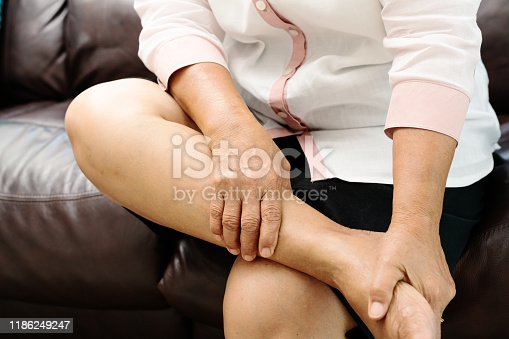 875123630istockphoto leg cramp, senior woman suffering from leg cramp pain at home, health problem concept 1186249247