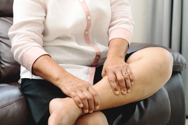 leg cramp, senior woman suffering from leg cramp pain at home, health problem concept stock photo