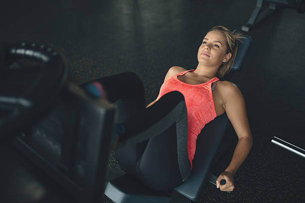 Leg day for beautiful woman Leg day for beautiful blond woman exercise machine stock pictures, royalty-free photos & images