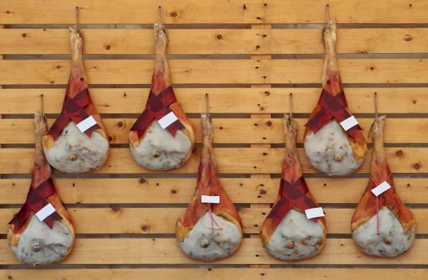 bein schinken prosciutto san daniele, eine ausgezeichnete italienische rohschinken-qualität hängt an einer holzwand - friaul julisch venetien stock-fotos und bilder