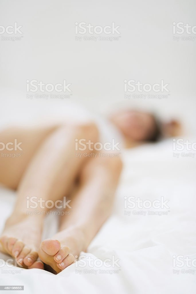 Leg of female laying on bed. Closeup stock photo