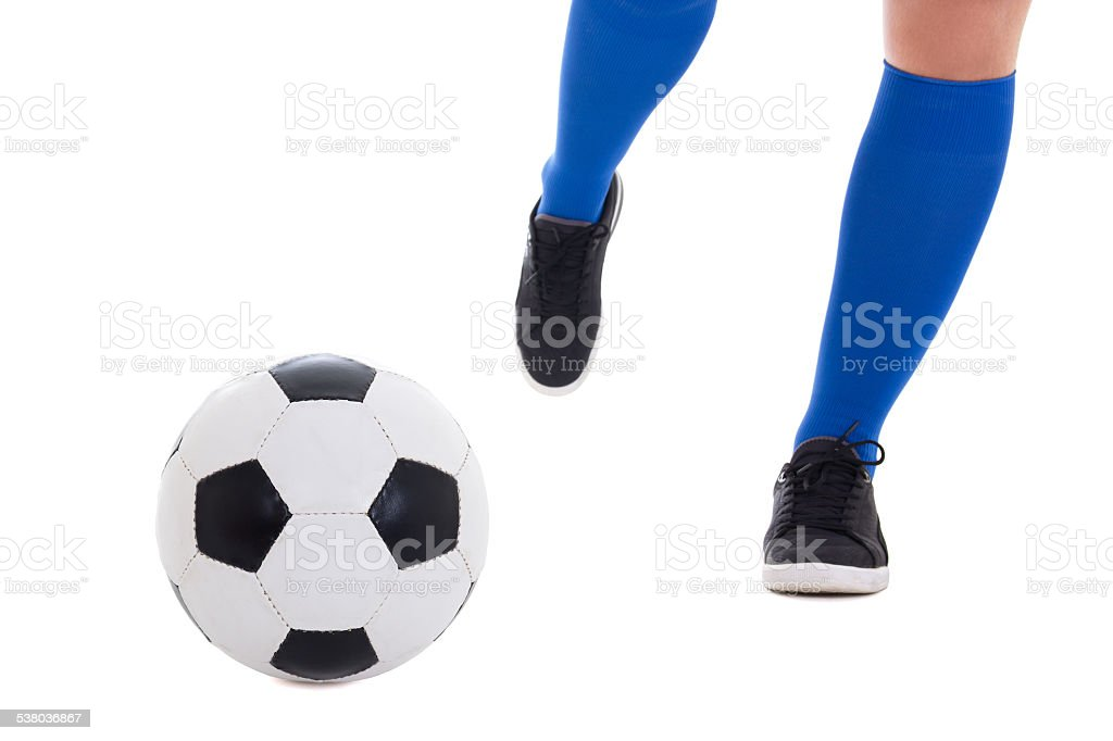 leg of soccer player in blue gaiters kicking ball stock photo
