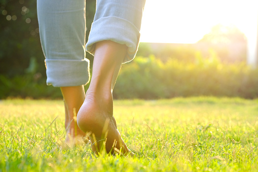 Leg of woman is on the ground. She is about to walk down the grass to exercise in the morning. Health and Relaxation Concepts