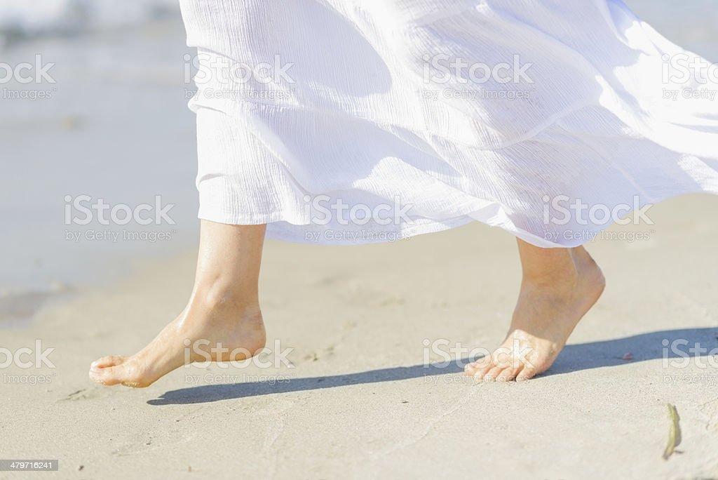Leg of young woman on sea coast. Closeup stock photo