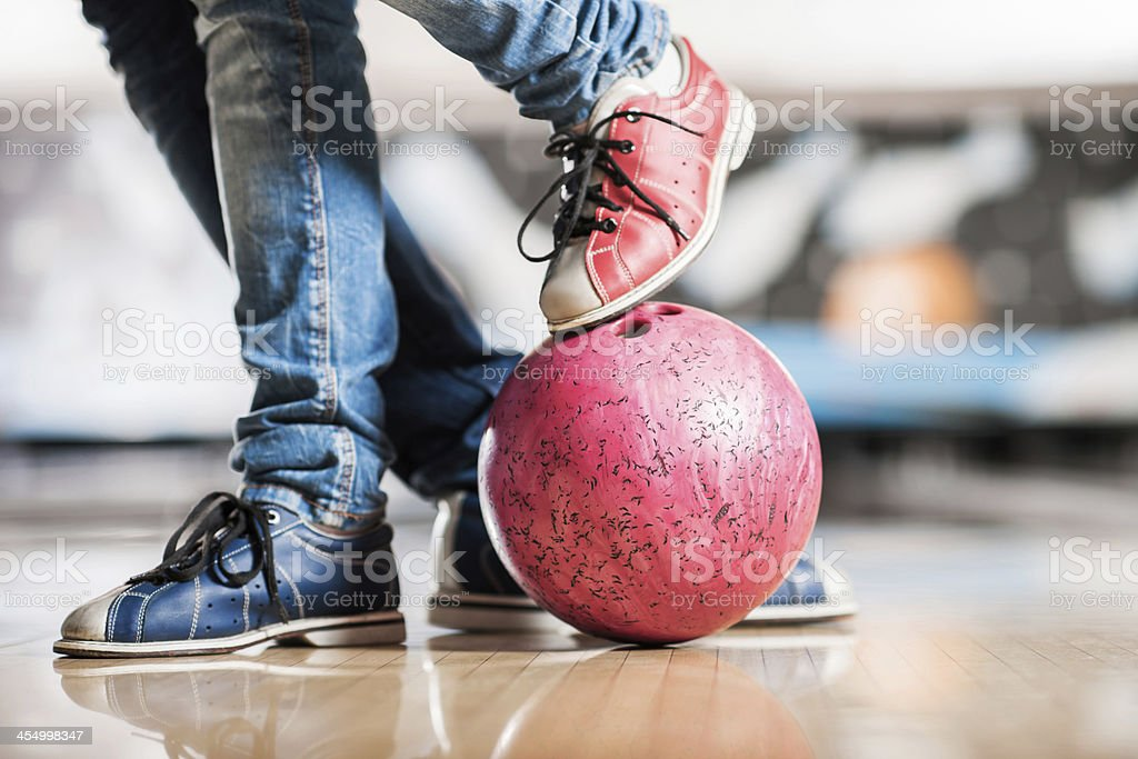 Unrecognizable person\'s leg on a bowling ball.