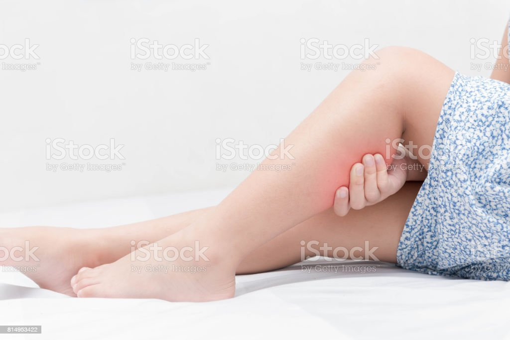 Leg pain in a girl on bed, stock photo