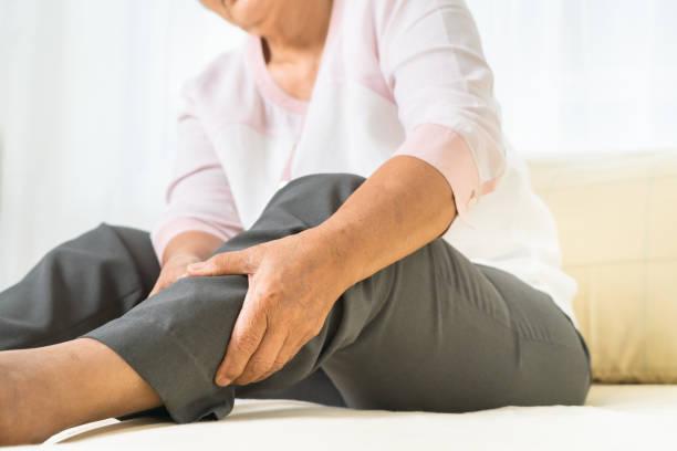 leg pain of senior woman at home, healthcare problem of senior concept stock photo