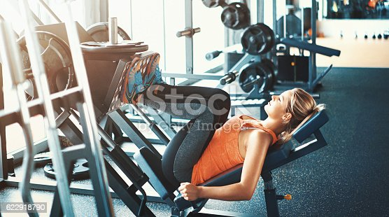 Closeup side view of mid 20's blond woman exercising on a leg press machine at a gym. She's wearing black track suit and orange sleeveless tank top. Blurry gym equipment in background.