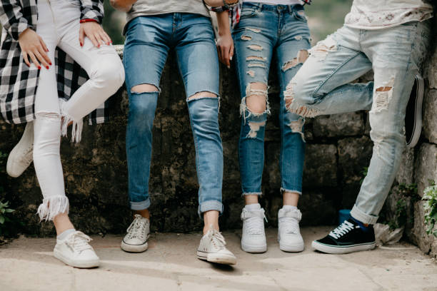 leg shot of four friends - jeans stock photos and pictures