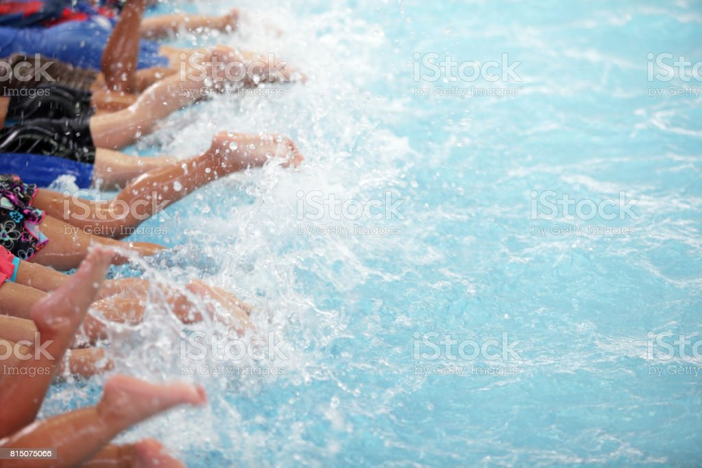 leg shot of kid at swimming pool class learning to swim stock photo