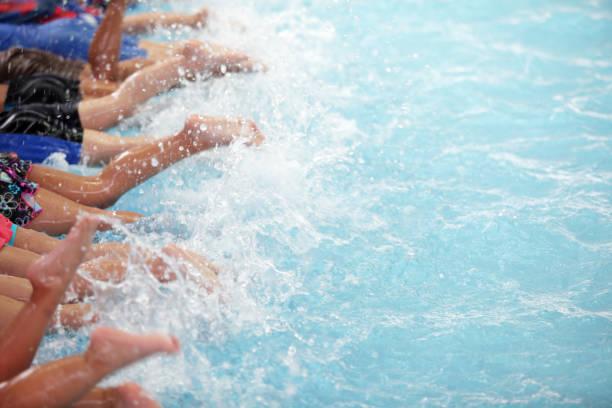 leg shot of kid at swimming pool class learning to swim stock photo