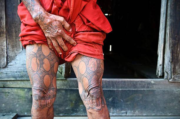 leg tattoos on burmese buddhist monk in mandalay - buddhist tattoos stock-fotos und bilder