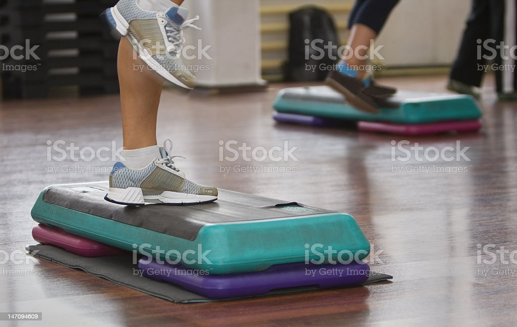 Leg view of people exercising on exercise steps in a class. stock photo