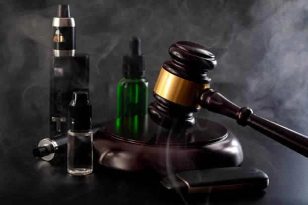 Acto legal para restringir el vapeo, prohibir fumar cigarrillos electrónicos y prohibir la legislación de prohibición de vapeo idea conceptual con el juez gavel, dispositivo vapeo, botella de e-juice y algunos aislados sobre fondo negro - foto de stock