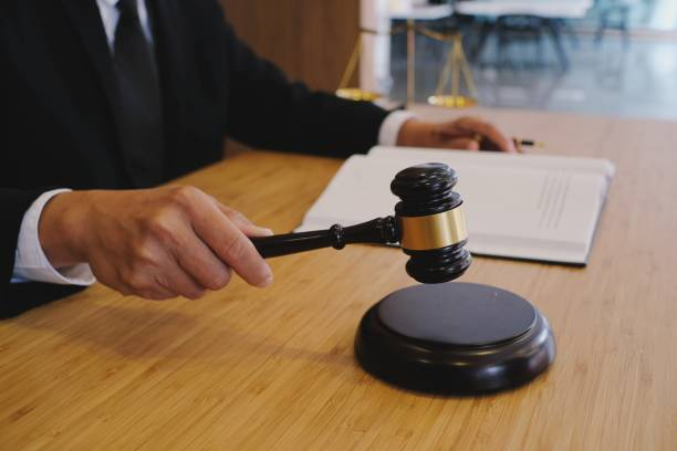 Legal counsel presents to the client a signed contract with gavel and legal law. justice and lawyer concept stock photo