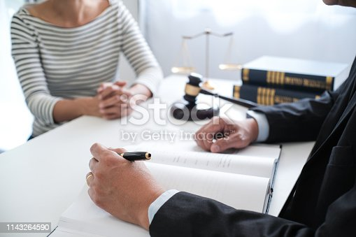 istock Legal counsel presents to the client a signed contract with gavel and legal law. justice and lawyer concept. 1143264590