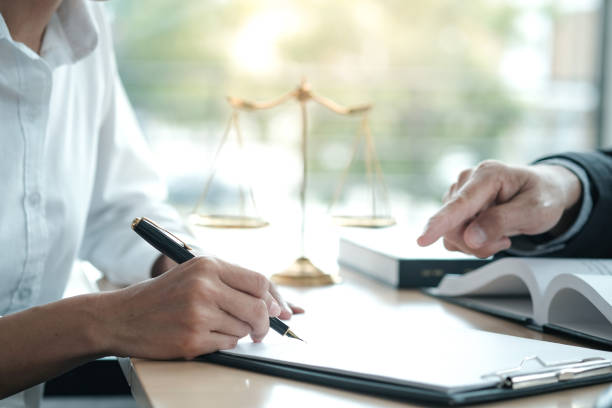 Legal counsel presents to the client a signed contract with gavel and legal law. justice and lawyer concept. stock photo