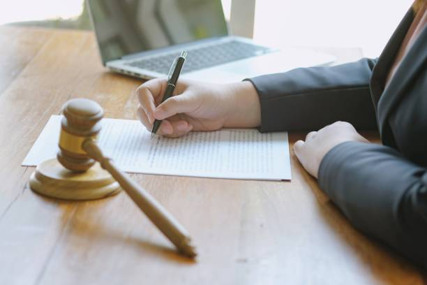 Legal counsel presents to the client a signed contract with gavel and legal law. justice and lawyer concept . stock photo