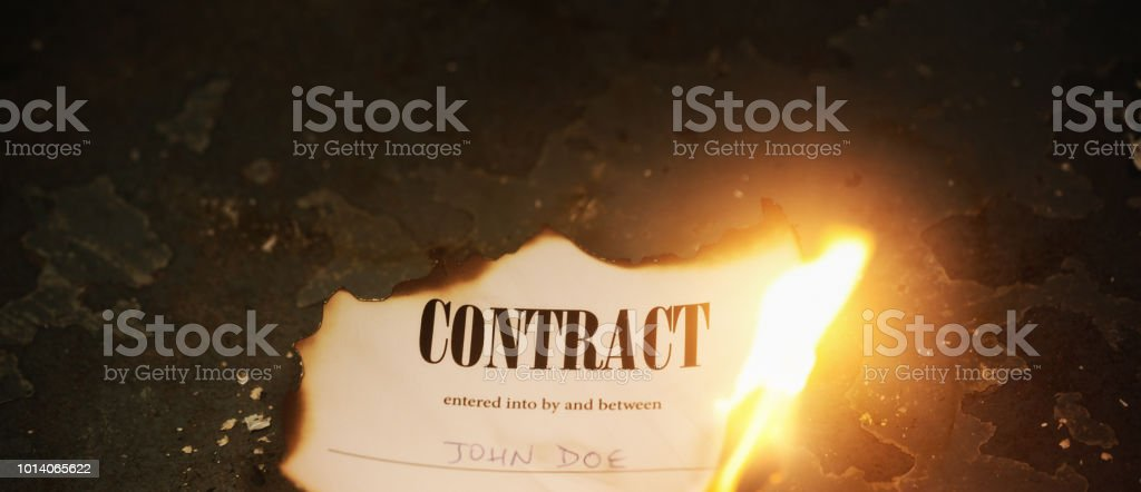 Legal document headed 'Contract' goes up in flames stock photo