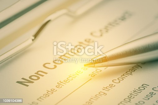 Legal form concept : Blue pen and a non compete contract on a clipboard. Noncompete contract is an agreement between employee and employer, not to enter into competition in subsequence business effort