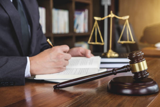 Legal law, advice and justice concept, Judge gavel with Justice lawyers, Counselor in suit or lawyer working on a documents in courtroom stock photo