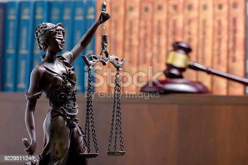 istock Legal Law concept - Open law book with a wooden judges gavel on table in a courtroom or law enforcement office. Copy space for text 922951124