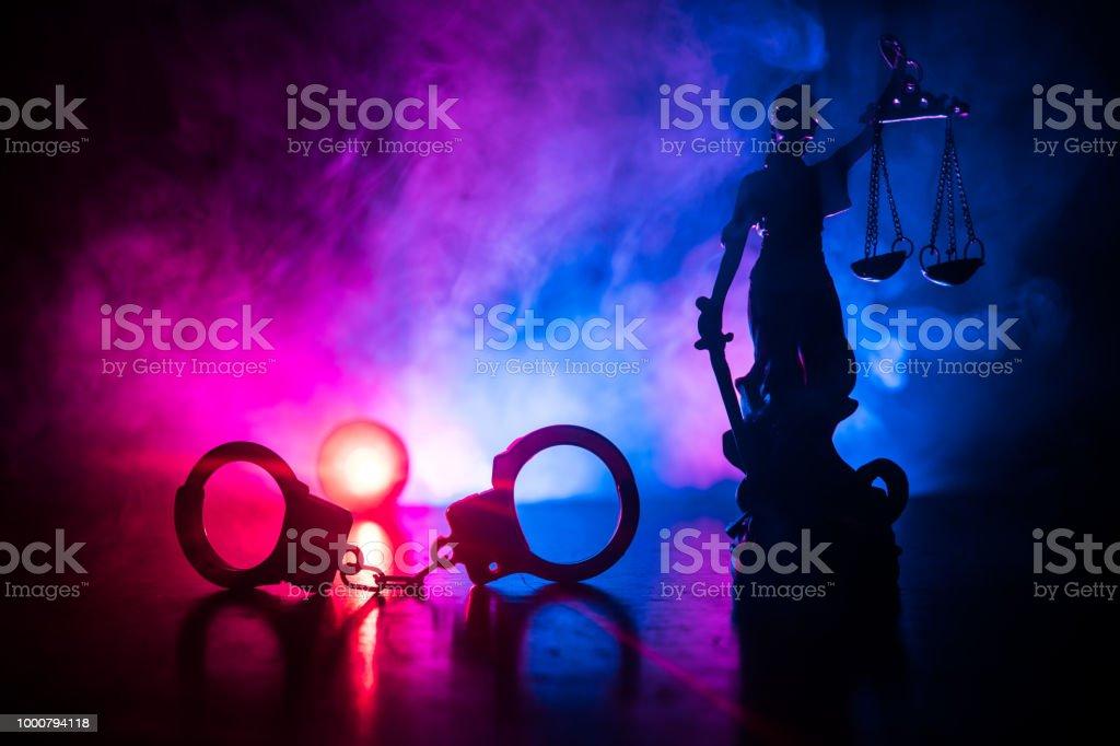 Concepto legal de la ley. Silueta de esposas con la estatua de la justicia en la parte trasera con las luces roja y azul de la policía en el fondo brumoso. - Foto de stock de Alemania libre de derechos