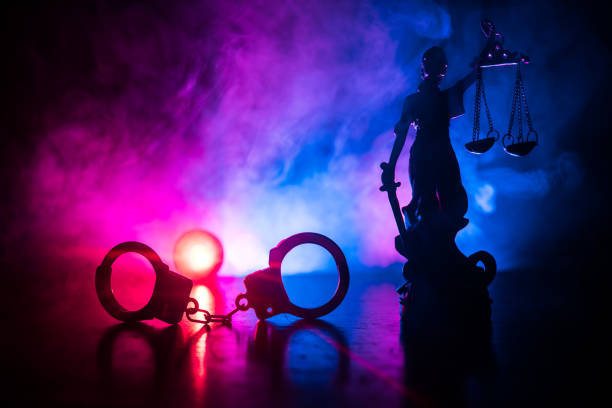 Legal law concept. Silhouette of handcuffs with The Statue of Justice on backside with the flashing red and blue police lights at foggy background. Legal law concept. Silhouette of handcuffs with The Statue of Justice on backside with the flashing red and blue police lights at foggy background. Selective focus arrest stock pictures, royalty-free photos & images
