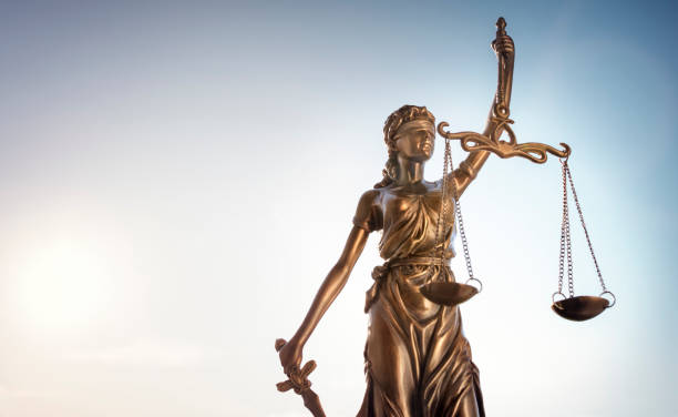 Legal law concept statue of Lady Justice with scales of justice sky background stock photo