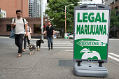 Seattle, USA - July 14, 2016: People passing a State Legal Marijuana shop sign on 2nd avenue late in the day in downtown.