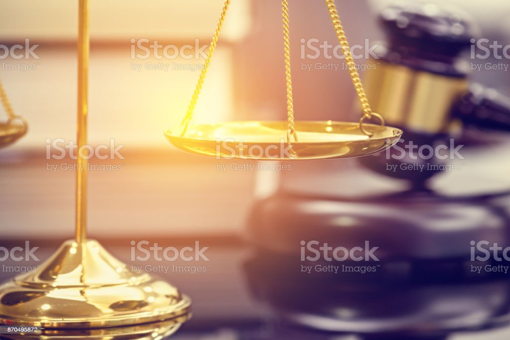 Legal office of lawyers, justice and law concept : Brass scales of justice with blurred wooden judge gavel or wood hammer and a soundboard on  judiciary desk in a courtroom with thick law books behind stock photo