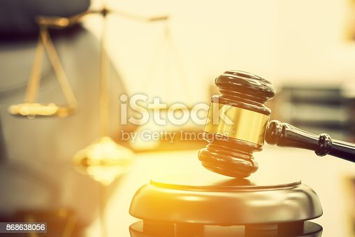 istock Legal office of lawyers, justice and law concept : Wooden judge gavel or a wood hammer and a soundboard used by a judge person on a desk in a courtroom with a blurred brass scale of justice behind. 868638056