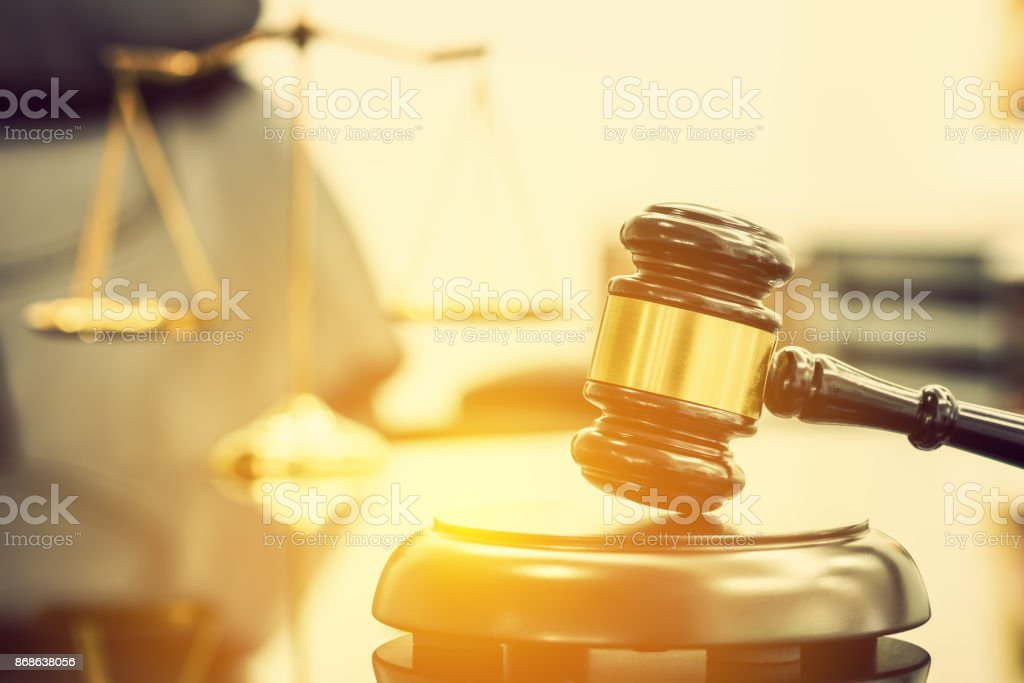 Legal office of lawyers, justice and law concept : Wooden judge gavel or a wood hammer and a soundboard used by a judge person on a desk in a courtroom with a blurred brass scale of justice behind. stock photo