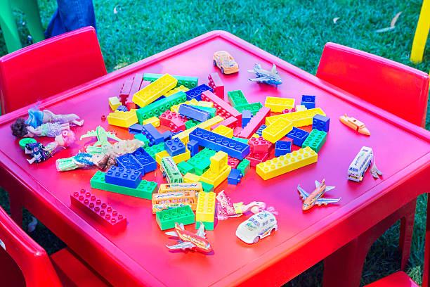 lego und anderen spielsachen auf einem spielzeug-tisch - lego flugzeug stock-fotos und bilder