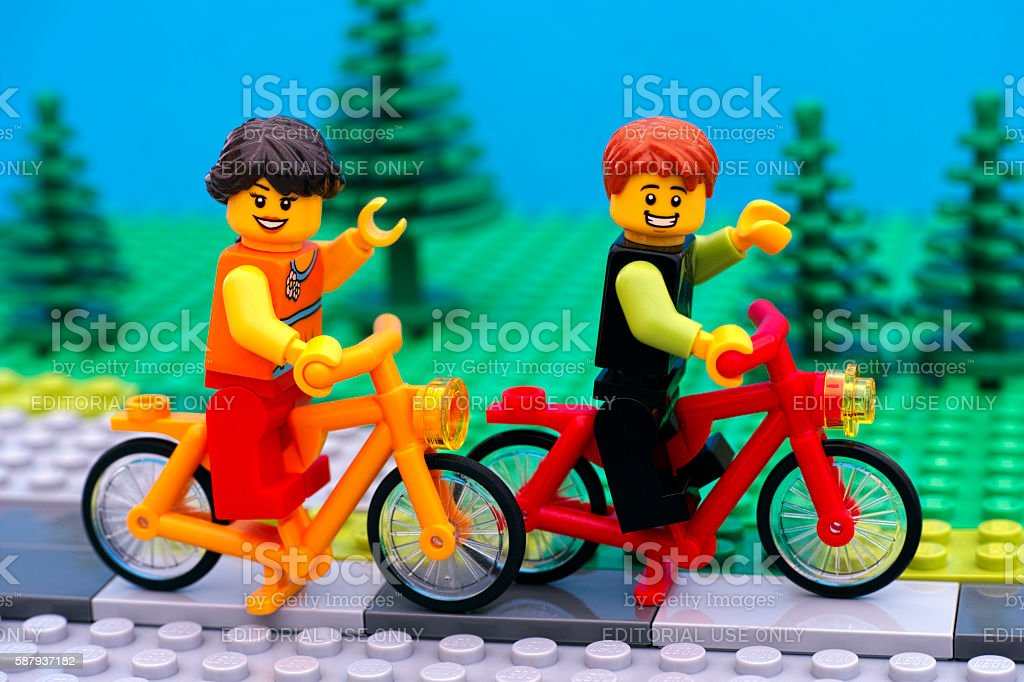 Lego boy and girl riding bikes in park stock photo
