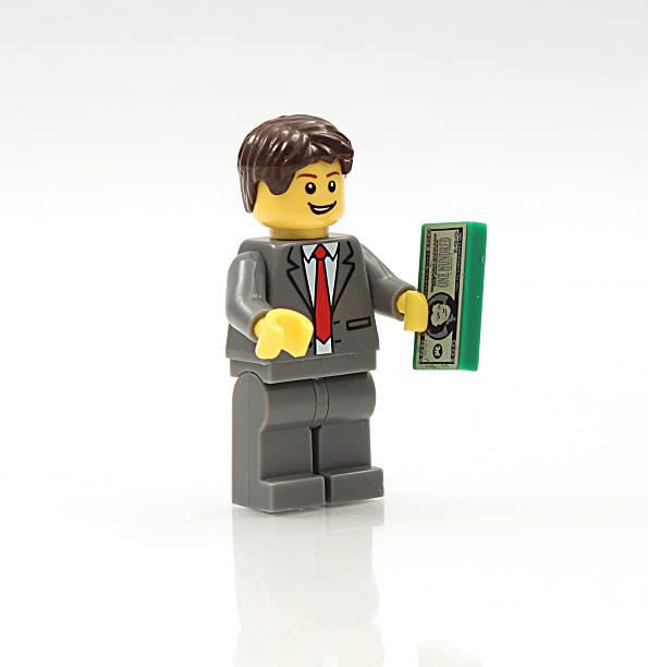 Lego Businessman holding money stock photo