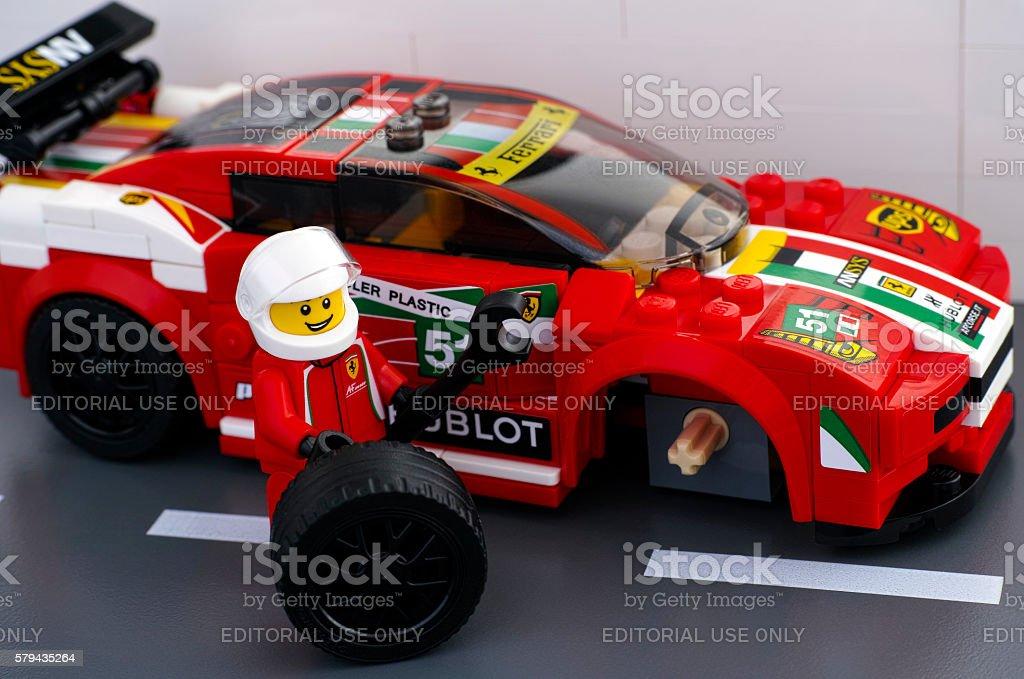 Lego driver fixing wheel of Ferrari 458 stock photo