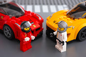 Tambov, Russian Federation - March 09, 2015: Lego drivers minifigures by LEGO Speed Champions and his car on background. There are Lego LaFerrari and Lego McLaren P1 cars models. Studio shot.