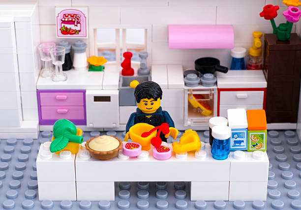 lego man cooking dessert in domestic kitchen - lego house stock photos and pictures