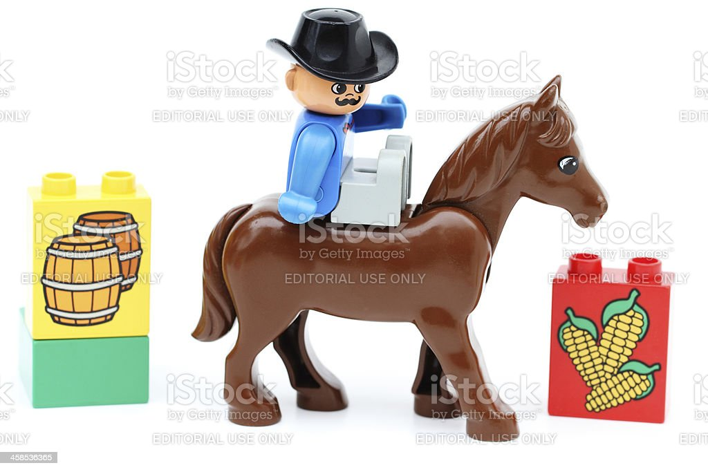 Lego man on horse with toy block pieces nearby stock photo