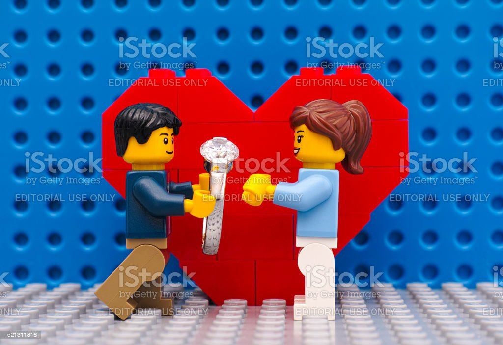 Lego man with ring makes marriage proposal stock photo